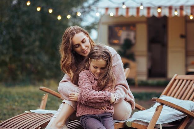 Mutter und kleine tochter, die spaß in der landschaft auf reisemobilferien sich entspannen und haben Premium Fotos