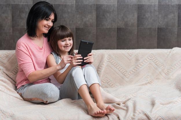Mutter und kleine tochter, die tablette auf couch verwendet Kostenlose Fotos