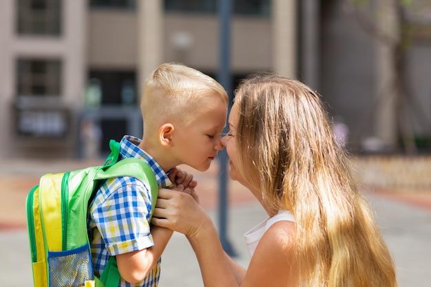 Mutter und kleiner sohn berühren nasen vor der schule Premium Fotos