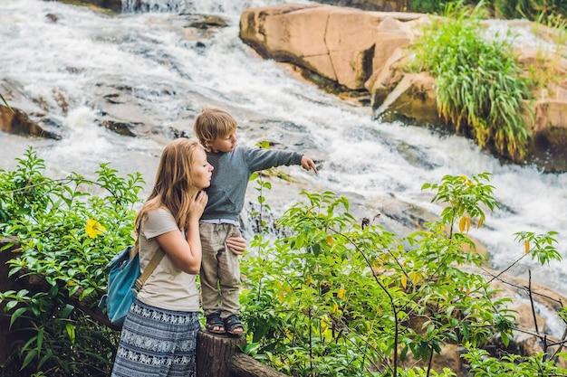 Mutter und sohn auf der oberfläche des schönen camly wasserfalls in da lat stadt, Premium Fotos
