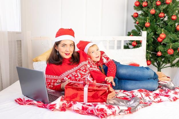 Mutter und sohn liegen auf dem bett in der nähe des weihnachtsbaumes Premium Fotos