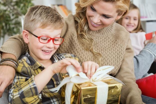 Mutter und sohn mit einem goldenen geschenk Kostenlose Fotos