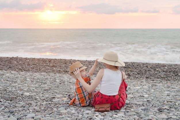 Mutter und sohn spielen am kiesstrand. sonnenuntergang rückansicht Premium Fotos
