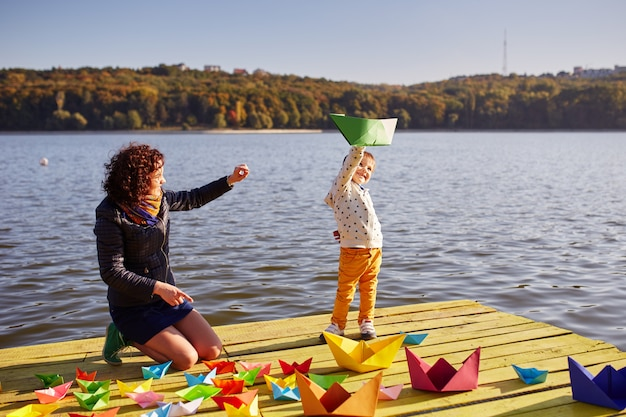 Mutter und sohn spielen mit papierbooten am see Kostenlose Fotos