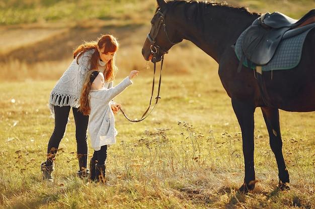 Mutter und tochter auf einem gebiet, das mit einem pferd spielt Kostenlose Fotos
