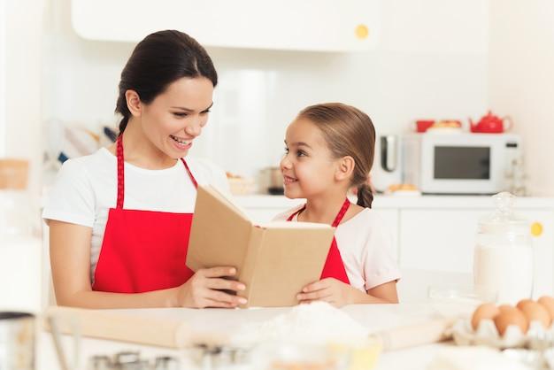 Mutter und tochter betrachten die rezepte im kochbuch Premium Fotos