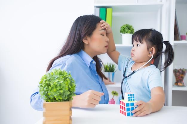 Mutter und tochter, die doktor mit stethoskop spielen Kostenlose Fotos