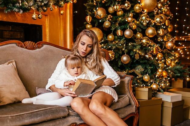 Mutter und tochter, die ein buch am kamin am weihnachtsabend lesen. verziertes wohnzimmer mit baum, kamin und geschenken. winterabend zu hause für eltern und kinder. Premium Fotos