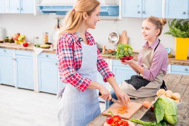 Mutter und tochter, die einander beim zubereiten des lebensmittels in der küche betrachten Kostenlose Fotos