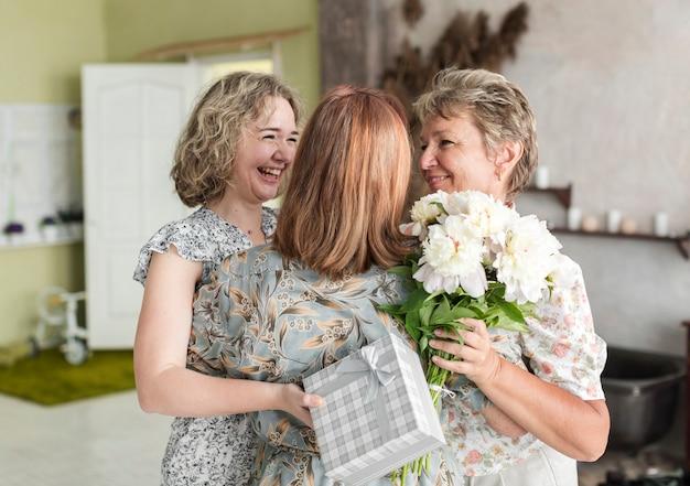 Mutter und tochter, die ihre großmutter mit geschenk- und blumenblumenstrauß zu hause halten umarmen Kostenlose Fotos