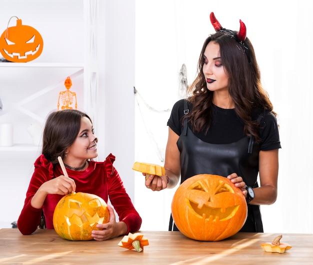 Mutter und tochter, die kürbise für halloween schnitzen Kostenlose Fotos