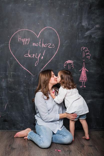 Mutter und tochter, die nahe glücklicher mutter-tagesaufschrift küssen Kostenlose Fotos