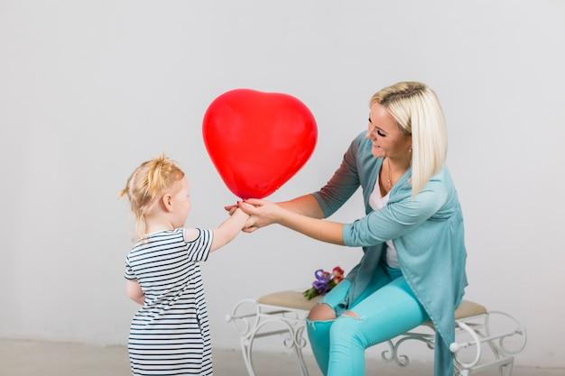 Mutter und tochter, die roten herzballon halten Kostenlose Fotos