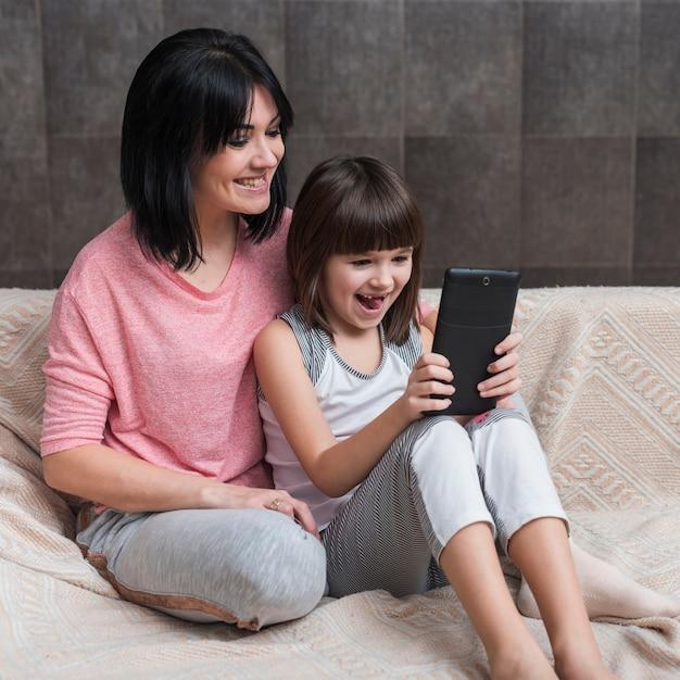 Mutter und tochter, die tablette auf couch verwendet Kostenlose Fotos