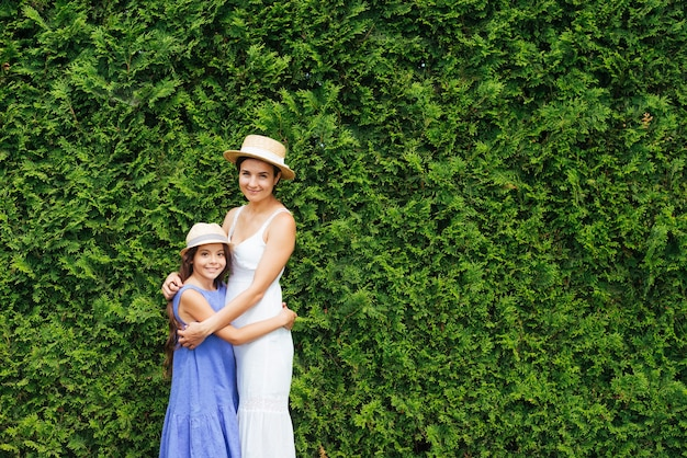 Mutter und tochter, die vor büschen umarmen Kostenlose Fotos
