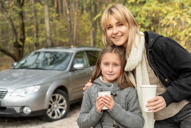 Mutter und tochter, die weiße becher anhalten Kostenlose Fotos