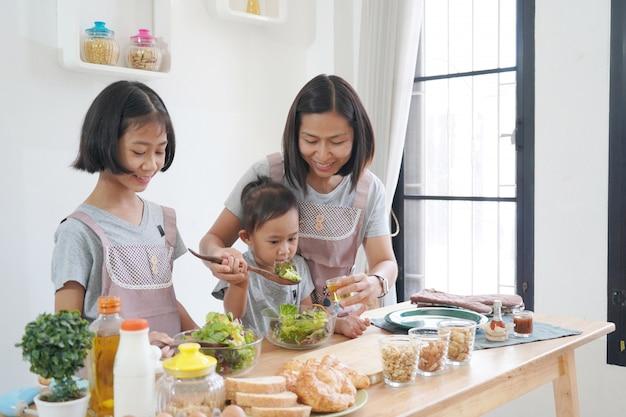 Mutter und tochter, die zu hause in der küche, glückliches familienasiatkonzept kocht Premium Fotos