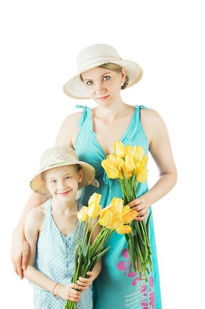 Mutter und tochter in der blauen kleidung und in den hüten lokalisiert auf weißem hintergrund. Premium Fotos