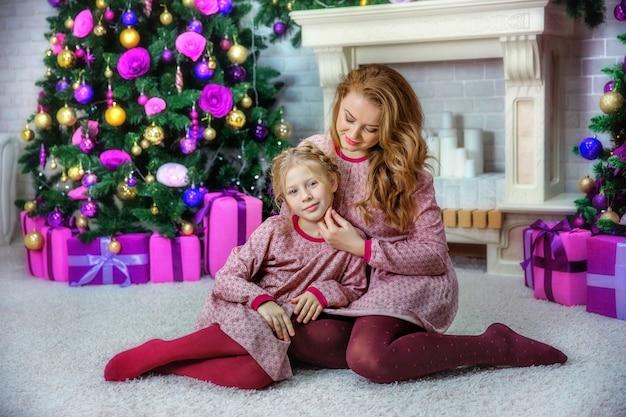Mutter und tochter in der nähe des weihnachtsbaumes im fotostudio Premium Fotos