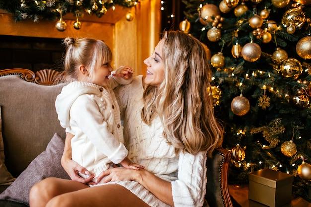 Mutter und tochter in der weißen strickenden kleidung umarmend und lächelnd, winter in einem verzierten wohnzimmer am weihnachtsabend zusammen glättend. familienglück Premium Fotos