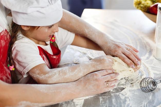 Mutter und tochter in derselben kleidung haben spaß daran, einen teig in einer gemütlichen küche zuzubereiten Kostenlose Fotos