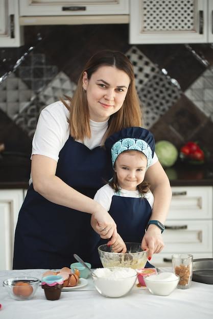 Mutter und tochter in identischen schürzen und kochmützen kochen in der küche Premium Fotos