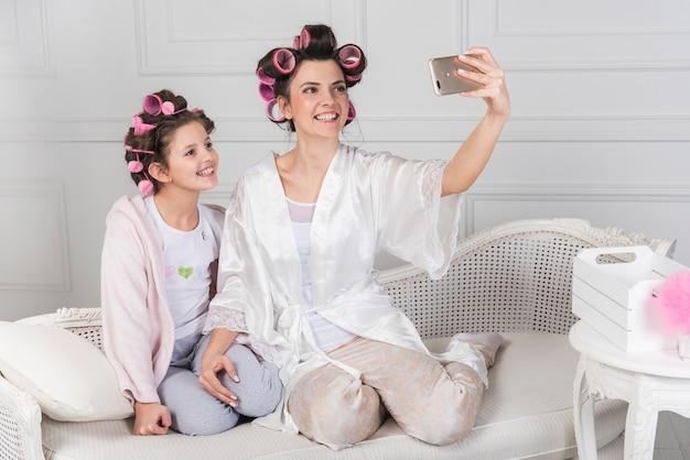 Mutter und tochter in lockenwicklern selfie nehmen Kostenlose Fotos
