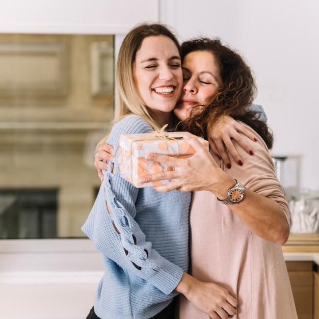 Mutter und Tochter mit dem Geschenk, das in der Küche umarmt Kostenlose Fotos