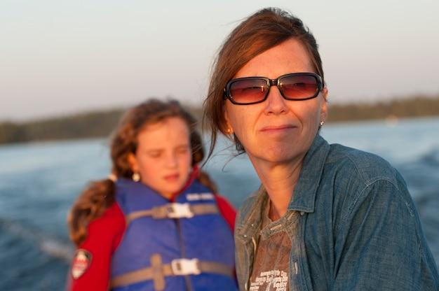 Mutter und tochter mit dem sonnenlicht in ihrem gesicht beim reiten in ein boot am see des holzes, ontario Premium Fotos