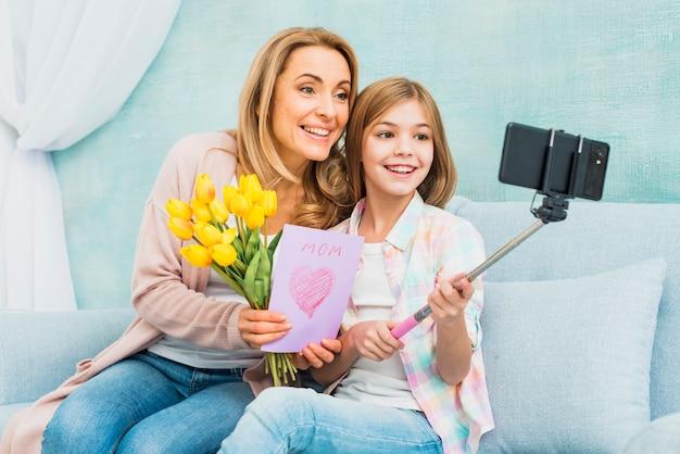 Mutter und tochter mit den geschenken, die selfie nehmen Kostenlose Fotos