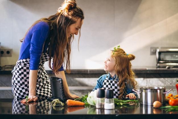 Mutter und tochter mit der tablette, die in der küche kocht Premium Fotos