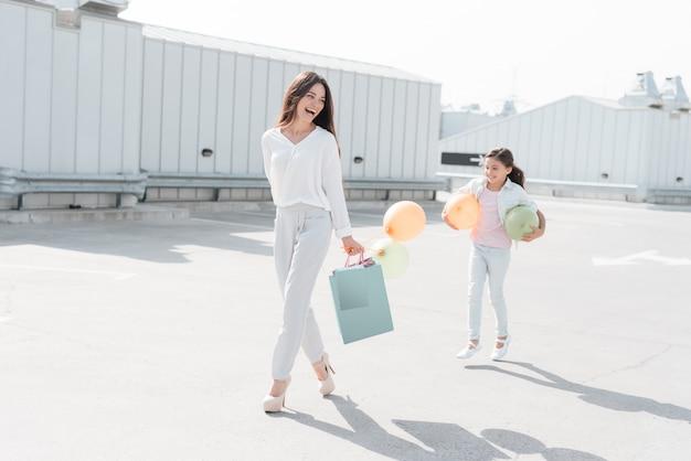 Mutter und tochter mit einkaufstüten gehen. Premium Fotos