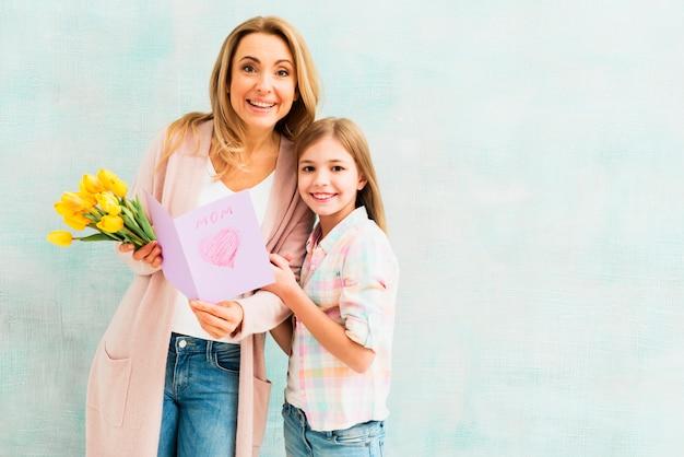 Mutter und tochter mit geschenken lächelnd und kamera betrachten Kostenlose Fotos