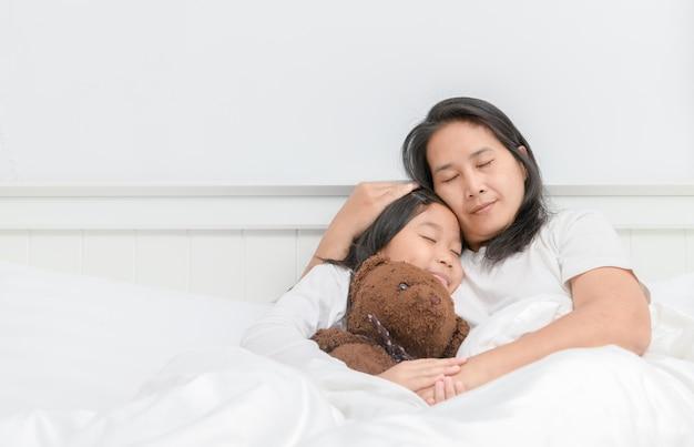 Mutter und tochter schlafen auf dem bett Premium Fotos