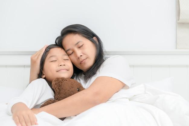 Mutter und tochter schlafen zusammen auf dem bett Premium Fotos