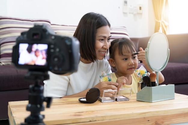 Mutter und tochter schminken sich. mit aufnahme machen video blogger kamera Premium Fotos