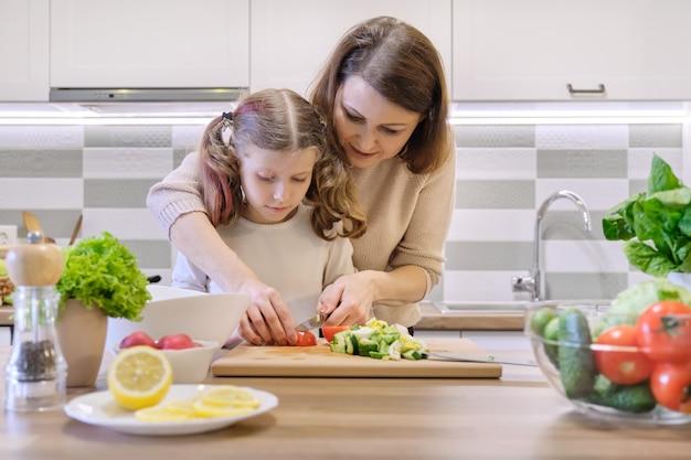 Mutter und tochter schnitten gemüse zu hause in der küche für salat. Premium Fotos
