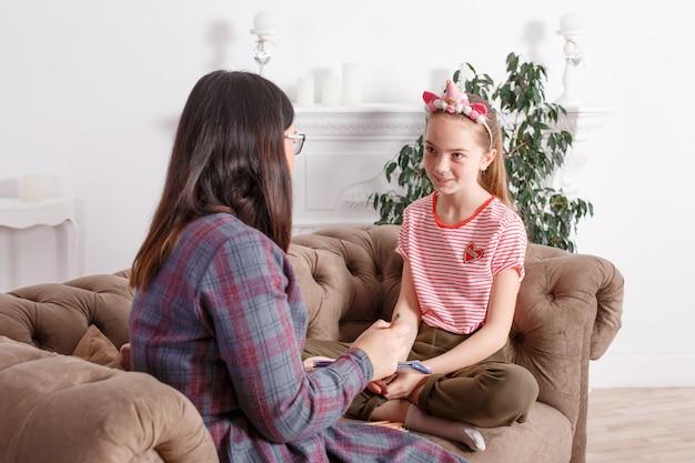 Mutter und tochter sitzen auf der couch und plaudern. mädchen teenager mit emotionen erzählt ihrer mutter eine geschichte. tochter teilt ihre gefühle mit ihren eltern. freizeit mütter und töchter Premium Fotos