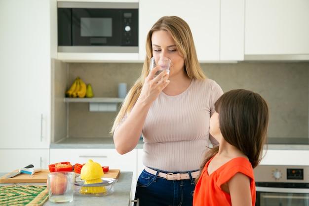 Mutter und tochter trinken wasser, während sie zitronensaft auspressen und salat zusammen in der küche kochen. familienkochen oder gesundes lebensstilkonzept Kostenlose Fotos