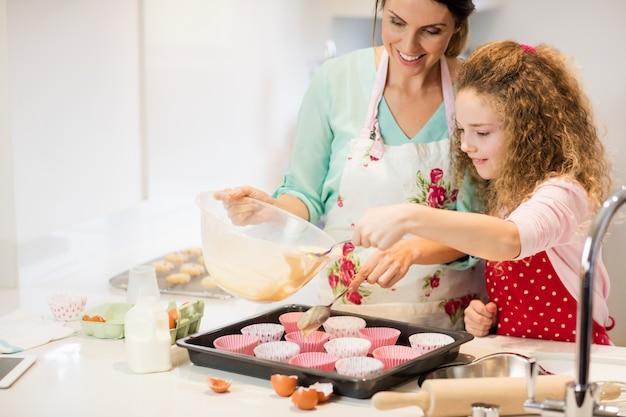 Mutter und tochter vorbereitung kleinen kuchen in der küche Kostenlose Fotos