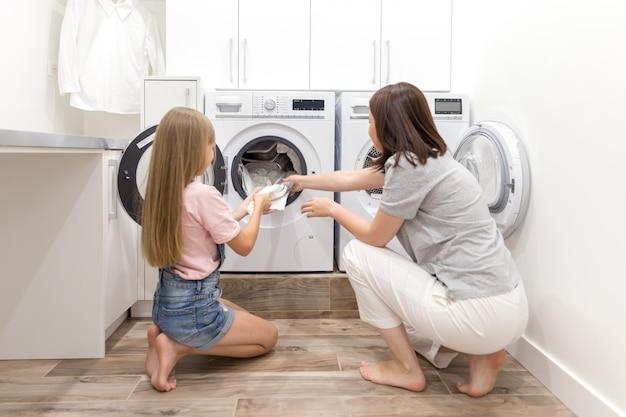 Mutter- und tochterhelfer in der waschküche nahe der waschmaschine und dem trockner, die saubere kleidung ausziehen Premium Fotos