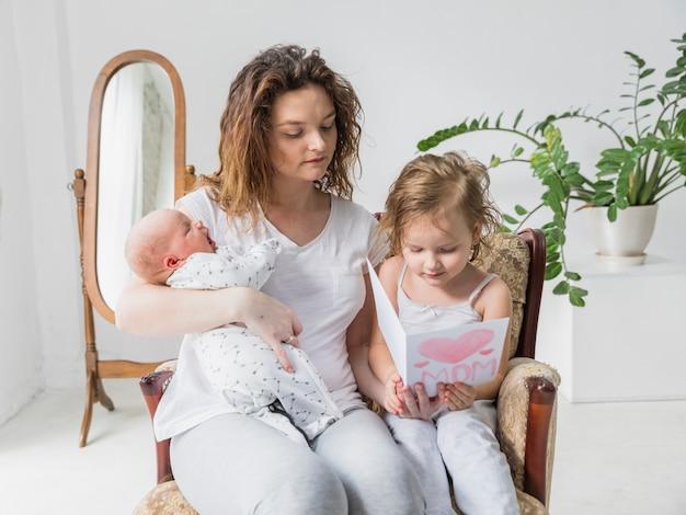Mutter- und tochterlesegrußkarte, die zusammen auf sessel im haus hält baby sitzt Kostenlose Fotos