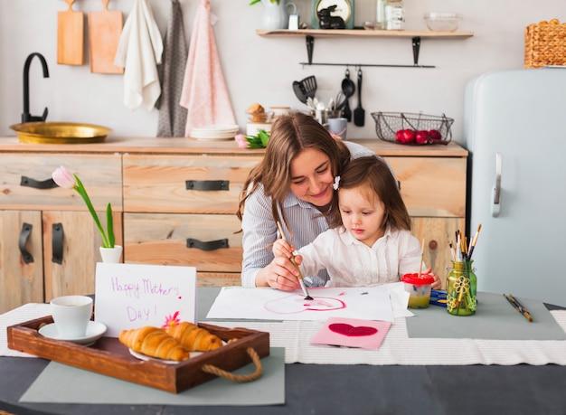 Mutter- und tochtermalereiherz bei tisch Kostenlose Fotos