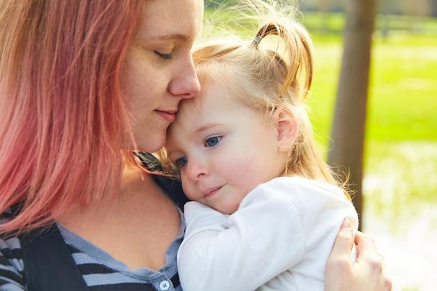 Mutter- und tochterportrait umarmen das küssen im park Premium Fotos
