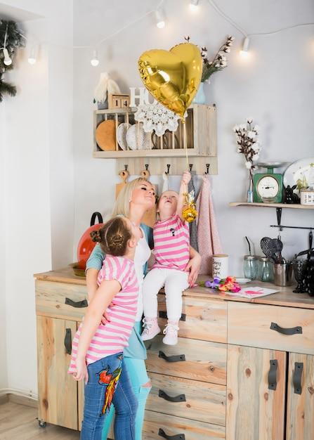 Mutter und töchter mit herzballon in der küche Kostenlose Fotos
