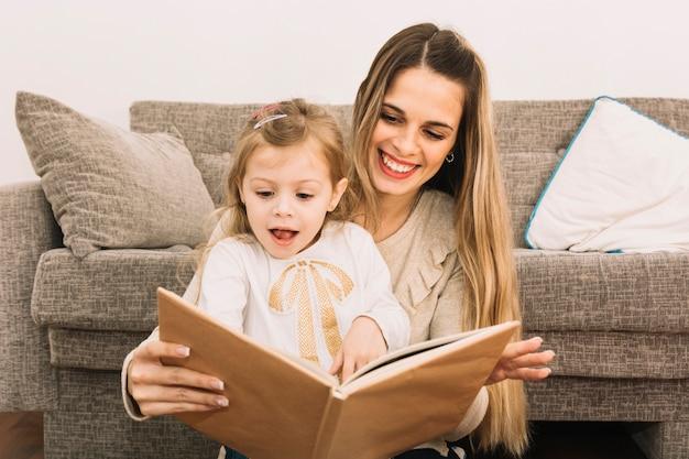 Mutter und überraschtes tochterlesebuch nahe couch Kostenlose Fotos