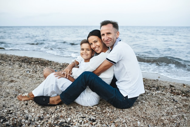 Mutter, vater und sohn sitzen am strand in der nähe des meeres, umarmen sich und schauen gerade Kostenlose Fotos