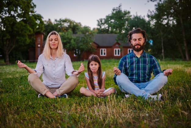 Mutter, vater und tochter kind meditieren zusammen in lotus position im freien. Premium Fotos
