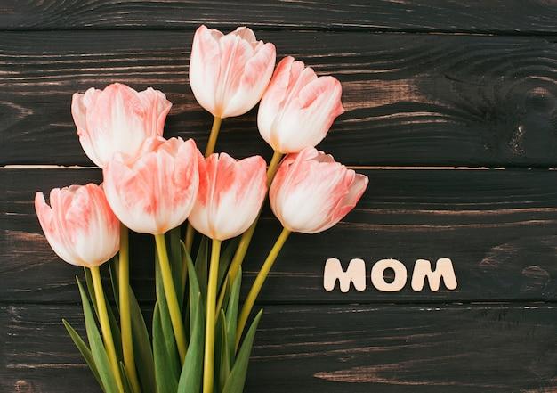 Mutteraufschrift mit tulpenblumenstrauß auf holztisch Kostenlose Fotos