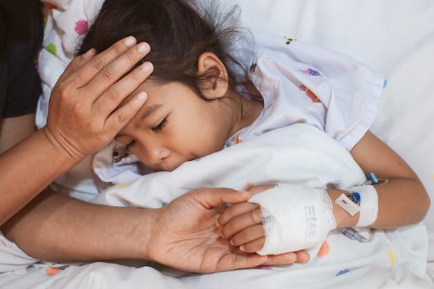 Mutterhand, die kranke tochterhand hält, die lösung iv verbunden hat Premium Fotos